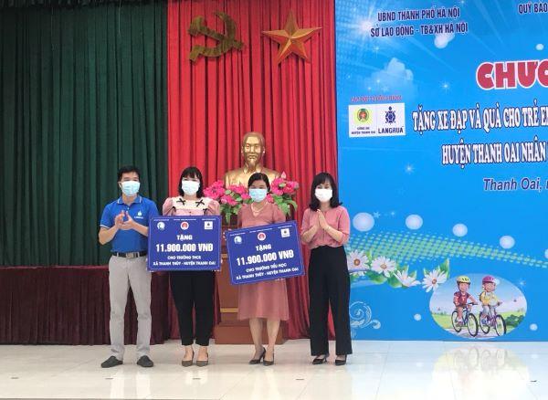 Tổng Giám đốc Công ty CP Làng Rùa và Phó phòng Bảo vệ chăm sóc trẻ em và Bình đẳng giới Đặng Ngọc Hà trao biển tượng trưng tặng xe rác và thùng rác cho trường THCS và tiểu học xã Thanh Thùy.